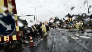 Työmiehet tekevät asfalttia sateisella säällä.