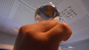 Käsi pitelee vettä täynnä olevaa lasia.
