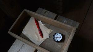 Puulaatikossa kello ja muistiinpanovälineet.