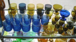 Suomalaista antiikkilasia, sinistä ja ruskeanvihertävää. Juomalaseja vitriinissä.
