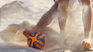 Pelaajat tavoittelevat palloa hiekalla.