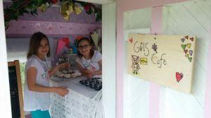 Kaksi tyttöä pitää kahvilaa leikkimökissä.