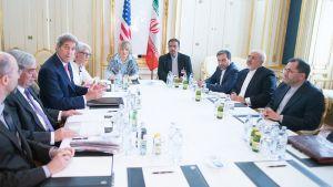 Miehiä ja naisia neuvottelupöydän äärellä.