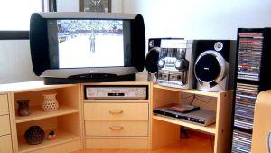 Valokuva olohuoneesta, jossa on suurikokoinen televisio, dc-soitin ja cd-teline.