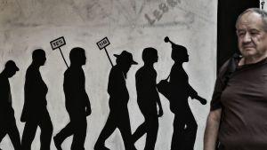 Mies kulkee graffitin ohi Ateenassa.