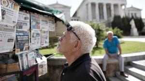 Mies katsoo seinälehteä Ateenassa.