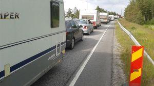 Kuvassa ruuhkaantunut liikenne. Asuntovaunuja ja autoja tiellä. Kuva menosuuntaan.