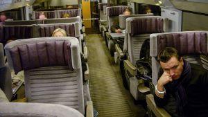 ihmisiä istuu junassa