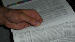 Mies selaa lakikirjaa.