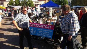 Kaksi miestä keskustelee torilla. Taustalla moottoripyörä, johon on kiinnitetty banderolli. Torin vilinää.
