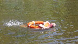 Lapsi ui selkää pelastusrenkaan kanssa.