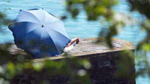 Nainen on piiloutunut sinisen sateenvarjon suojaan Saksan Lindaussa.