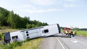 Ojaan kaatunut bussi onnettomuuspaikalla.