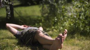 Mies makoilee nurmikolla auringossa.