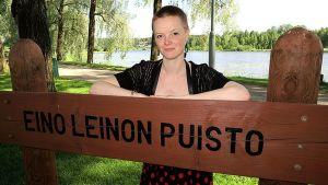 Nainen ja puiston nimikyltti.