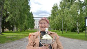 Kainuun ja Koillismaan murremestari, kuhmolainen Leena Romppanen voittopokaali sylissään Kajaanin seminaarin pihalla.