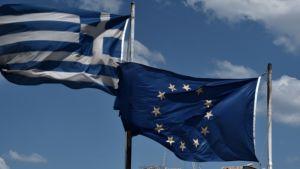 Kreikan ja EU:n liput liehuvat vierekkäin. Takana näkyy Ateenan Akropolis.