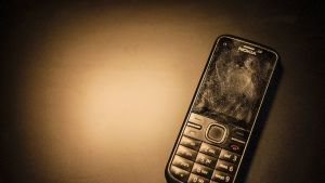 Kännykän näytössä on kaikenlaista pientä likaa ja rasvaisia sormenjälkiä.