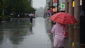 Ihmiset kävelevät sateessa kadulla sateenvarjon kanssa
