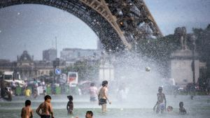 Ennätyshelteet koettelivat pariisilaisia kesäkuun lopussa. Turistit ja kaupunkilaiset vilvoittelevat Jardins du Trocadero-puistossa Eiffel-tornin juurella.