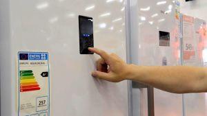 Kuvassa jääkaappeja ja käsi, joka näpyttelee jääkaapin näyttöä