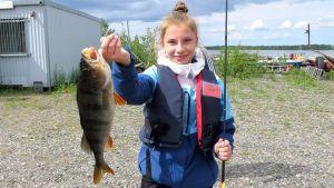 Kalastusleirin osallistuja Piia-Peppi Juntunen ahven kädessään.