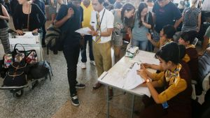 Lentoyhtiön työntekijät avustivat Balin lentokentällä odottavia matkustajia Indonesiassa 11. heinäkuuta.