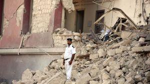 Poliisi seisoo vahdissa räjähdyksen aiheuttamilla raunioilla.