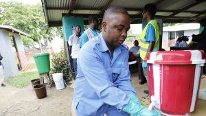 liberialainen mies desinfioi hanskojaan kloorivedellä