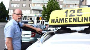 Taksiautoilija taksinsa vieressä