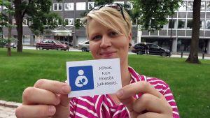 """Reeta Lahtinen näyttää korttia, jossa teksti """"Kiitos, kun imetät julkisesti."""""""