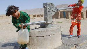 Kaksi lasta pumppaa vettä kaivosta.