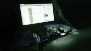 Huppupäinen hehnkilö istuu tietokoneen ääressä pimeässä.