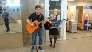 Oulun kaupungin palkkaamat nuoret Pirkka Lepola ja Julia Sundberg esiintyvät kirjaston ala-aulassa
