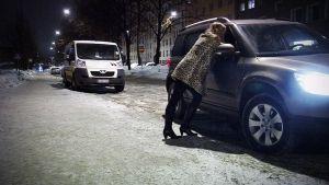 Prostituiotu nainen nojaa autoon kadulla Helsingissä.