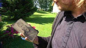 mies pitää kädessään vanhalla tekniikalla otettua valokuvaa.