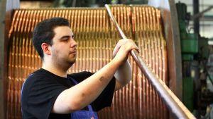 Mies tarkistaa kuparikaapelia, jota vedetään takana olevalle suurelle kuparikaapelikerälle.