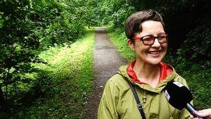 Hymyilevä nainen vehreällä metsätiellä.