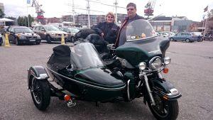 Nainen ja mies seisovat sivuvaunullisen moottoripyörän takana