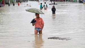 Ihmiset kahlaavat vedessä, tulvivalla kadulla Myanmarissa.