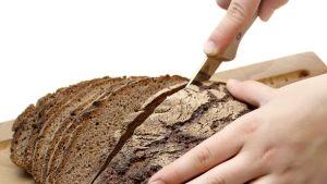 Poika leikkaa ruisleipää