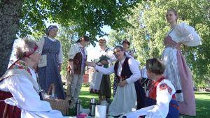 Joukko naisia kansallispuvuissa piknikillä.