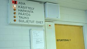 Kainuun käräjäoikeuden istuntosalin ovi.