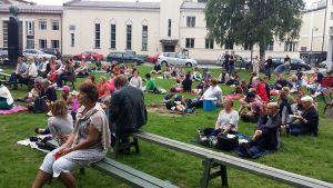 Ihmisiä puistossa piknikillä.