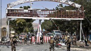 Afganistanin turvallisuusjoukkojen jäsenet tutkivat pommi-iskun tapahtumapaikkaa Kabulin lentokentän lähellä.