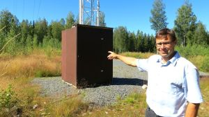 Mies osoittaa kädellä tuulen mittausasemaa