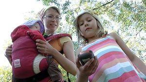 Mila Auvomaa kantaa sylirepussa perheen nuorimmaista Kieloa, kun Selja tarkkailee gps-laitetta.