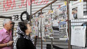 Kreikkalaiset tutkivat sanomalehtien kansia Ateenassa.