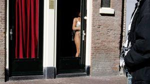 Prostituoitu työskentelee De Wallen punaisten lyhtyjen alueella alueella Amsterdamissa.
