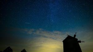 Linnunrata, tähdenlento ja tuulimyllyjä Hollannissa yötaivaalla.